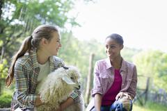 Two girls on a farm, one petting a goat Stock Photos