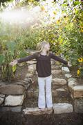 A child in a garden with sunflowers - stock photo