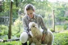 A teenager petting an angora goat Stock Photos