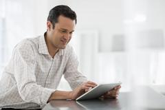 A man in an office using a tablet - stock photo