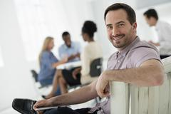A group with one person using a tablet - stock photo
