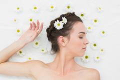 Stock Photo of Beautiful young woman with flowers in beauty salon