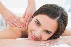 Stock Photo of Smiling woman enjoying shoulder massage at beauty spa