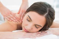 Stock Photo of Beautiful woman enjoying shoulder massage at beauty spa