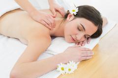Woman enjoying back massage at beauty spa Stock Photos