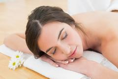Stock Photo of Woman resting with eyes closed on towel at beauty spa