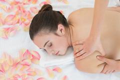 Woman enjoying back massage at beauty spa - stock photo