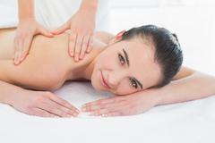 Beautiful woman enjoying back massage at beauty spa Stock Photos