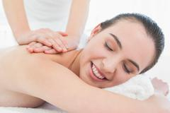 Beautiful woman enjoying back massage at beauty spa - stock photo