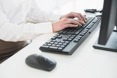 Mid section of businesswoman using computer keyboard in office Stock Photos