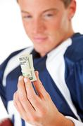 football: player looking at roll of cash - stock photo