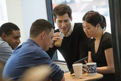 A group of people at a cafe with a digital tablet Stock Photos