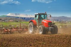 Brand new red tractor on the field working on land Stock Photos