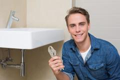 Smiling plumber with wrench by sink in bathroom - stock photo