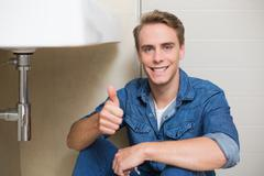 Handsome plumber gesturing thumbs up besides washbasin Stock Photos