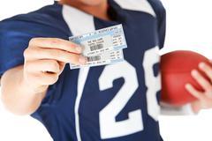 football: holding game day tickets - stock photo