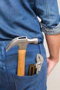Several tools in a man's rear denim pocket Stock Photos