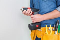 Mid section of a handyman with drill and toolbelt - stock photo