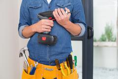Mid section of a handyman with drill and toolbelt Stock Photos