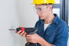 Serious young handyman using a drill - stock photo