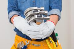 Mid section of handyman holding hammers with toolbelt around waist Stock Photos