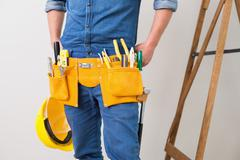 Mid section of a handyman with toolbelt and hard hat Stock Photos