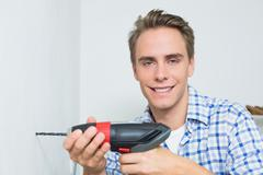 Portrait of handyman using a cordless drill to the wall - stock photo