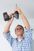 Handyman using a cordless drill to the ceiling - stock photo