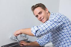 Smiling plumber fixing water tap with pliers - stock photo