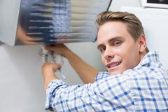 Stock Photo of Plumber repairing washbasin drain in bathroom