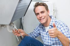 Plumber repairing washbasin drain while gesturing thumbs up Stock Photos