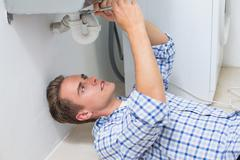 Plumber repairing washbasin drain in bathroom Stock Photos