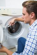Technician repairing a washing machine Stock Photos