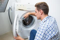 Technician repairing a washing machine - stock photo