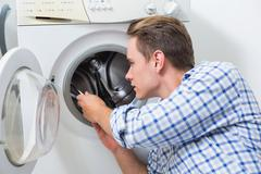 Stock Photo of Technician repairing a washing machine