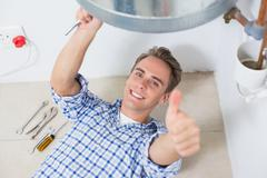 Technician gesturing thumbs up by hot water heater Stock Photos