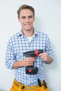 Portrait of a smiling handsome young handyman holding drill Stock Photos
