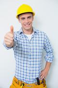 Stock Photo of Portrait of a handyman in yellow hard hat gesturing thumbs up