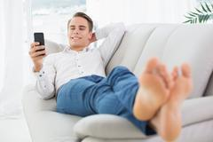 Relaxed man lying on sofa and text messaging Stock Photos