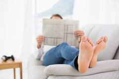 Full length of a relaxed man reading newspaper on sofa Stock Photos