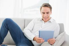 Stock Photo of Casual young man using digital tablet on sofa