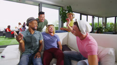 Happy group of friends socializing together in contemporary home Stock Footage