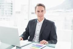 Smiling young businessman with laptop at office desk Stock Photos