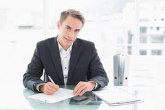 Smiling businessman writing documents at office desk Stock Photos