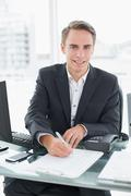 Businessman in front of computer writing document at office desk Stock Photos
