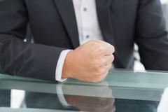 Mid section of businessman with clenched fist on office desk Stock Photos