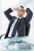 Worried young businessman at office desk Stock Photos