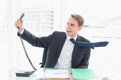 Businessman shouting as he holds out phone at office Stock Photos