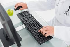Mid section of doctor using computer Stock Photos