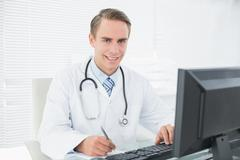 Smiling doctor writing note while using computer at medical office Stock Photos